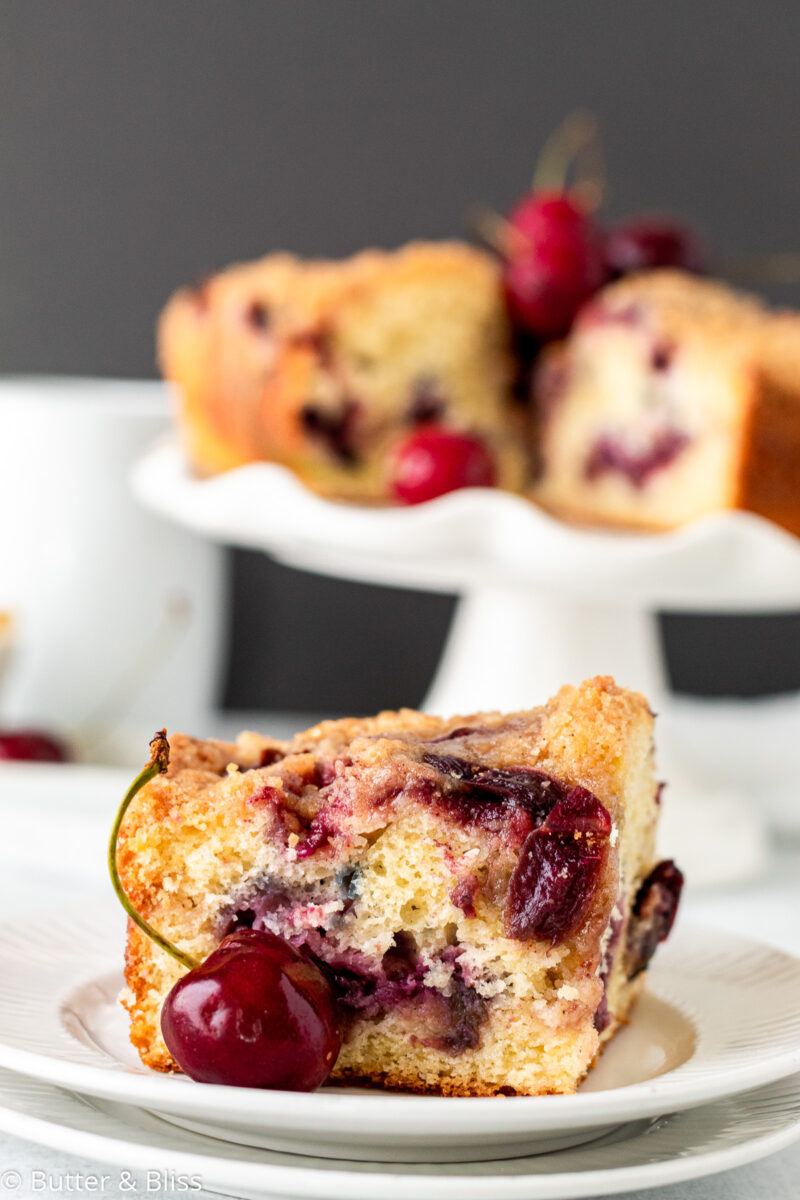 A slice of cherry coffee cake on a plate