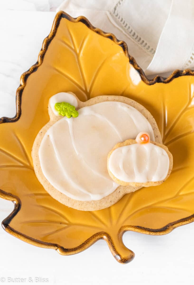 A decorated pumpkin cookie on fall plate