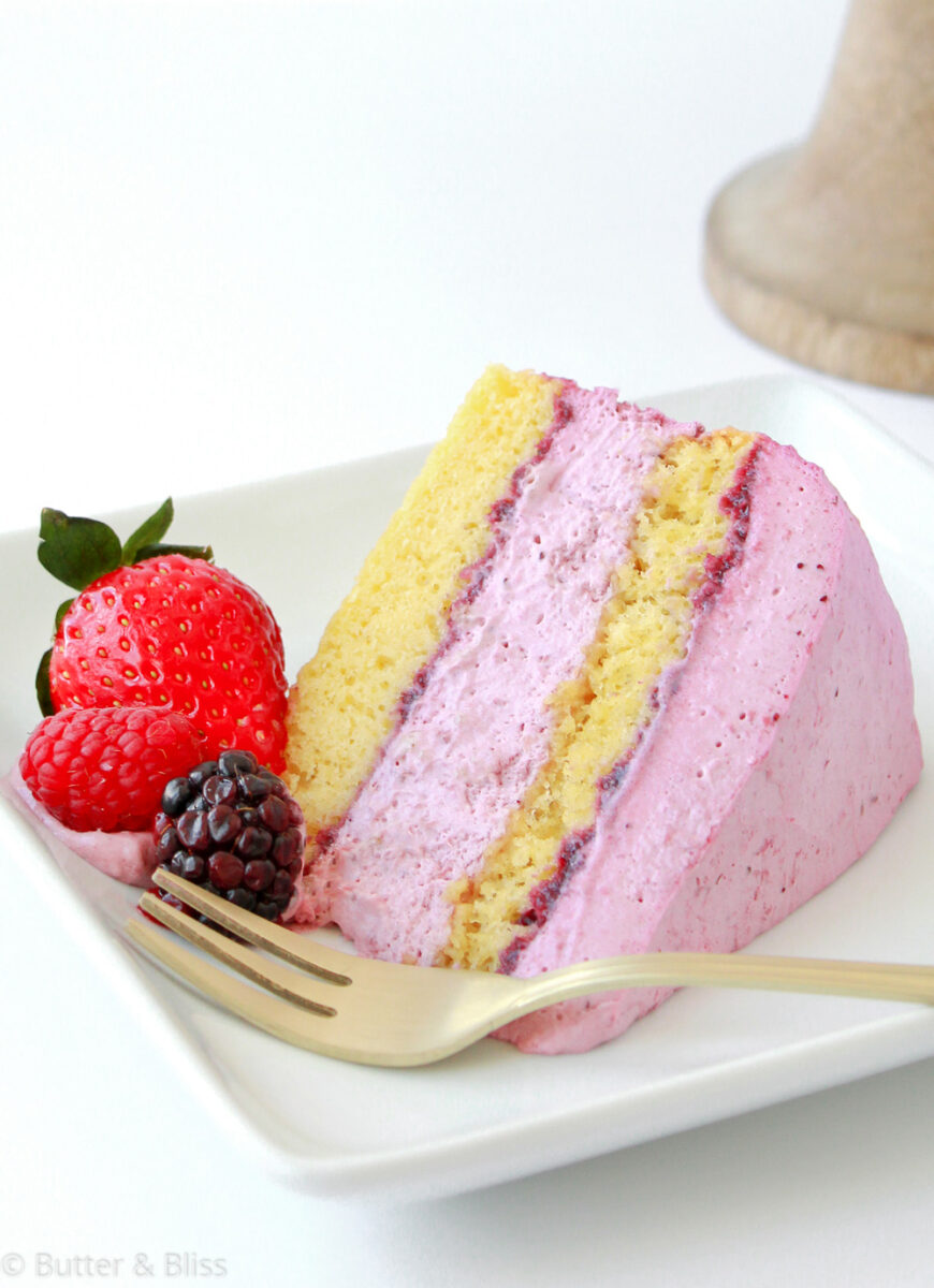 A slice of layer cake with creamy fruit filling and fresh fruit