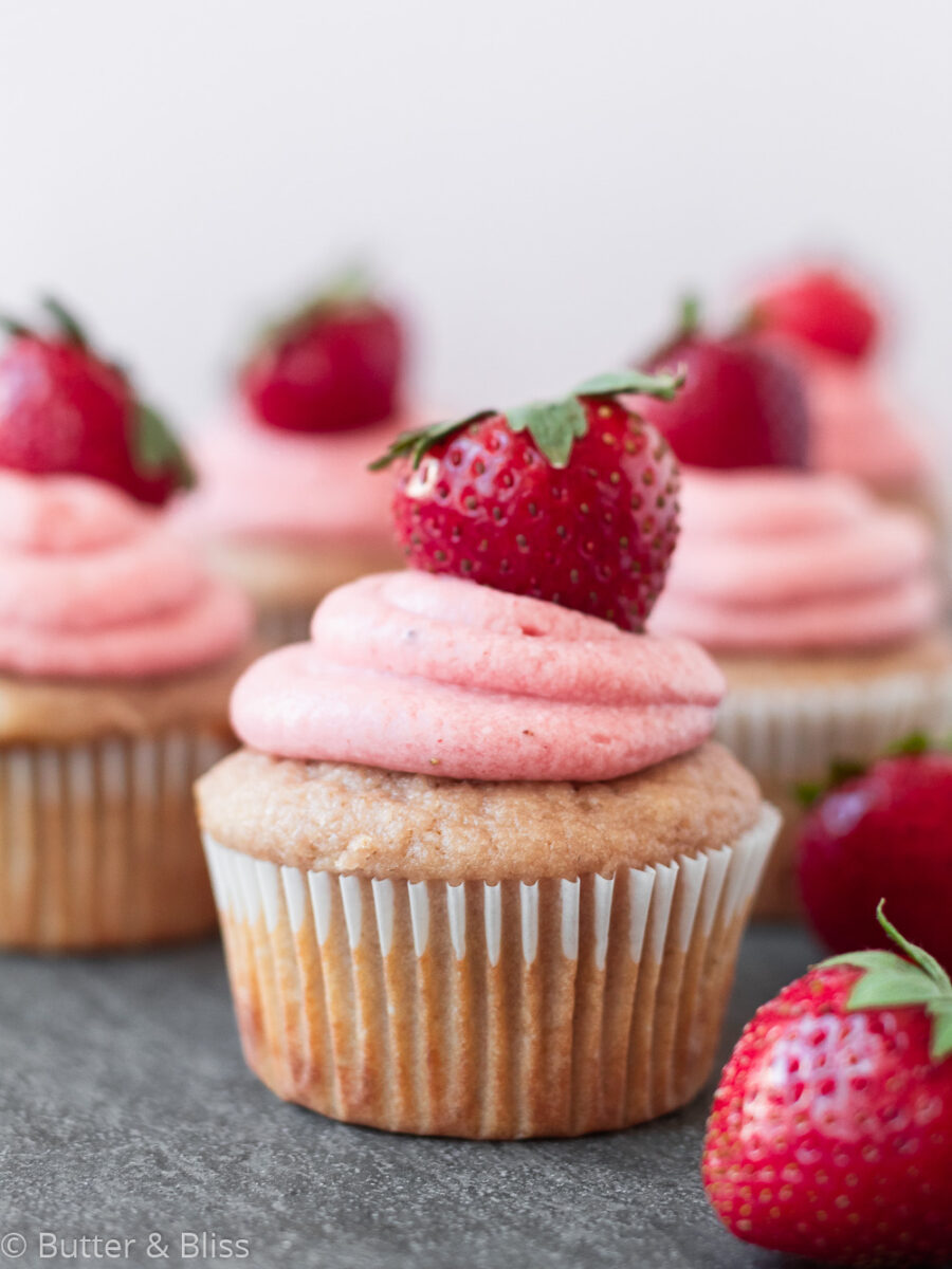 Frosted strawberry cupcake with a fresh strawberry