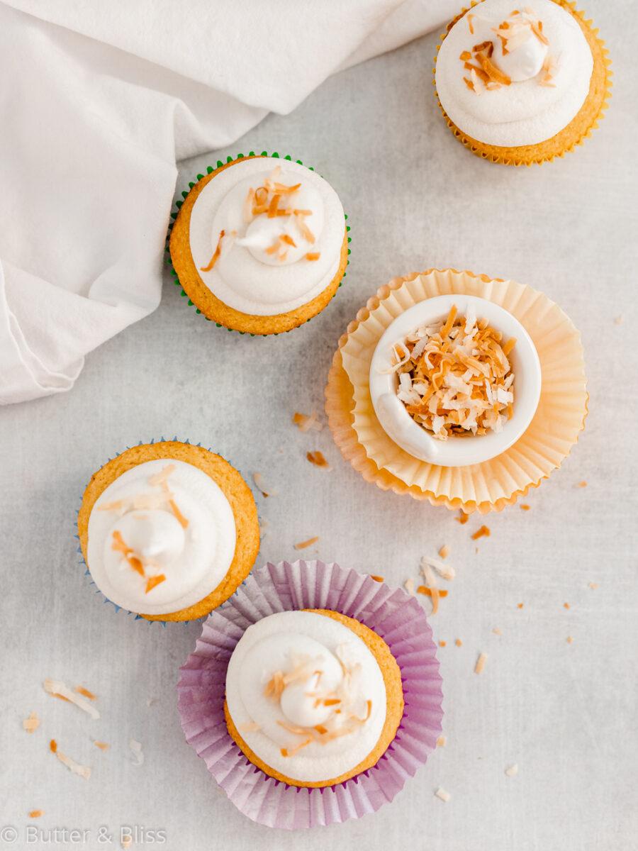4 vanilla cupcakes on a table