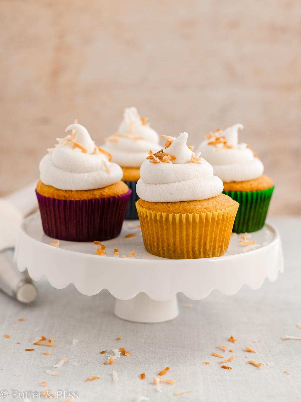 Frosted vanilla and coconut cupcakes on a platter