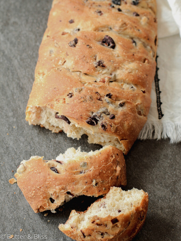 Loaf of kalamata and onion bread with torn pieces