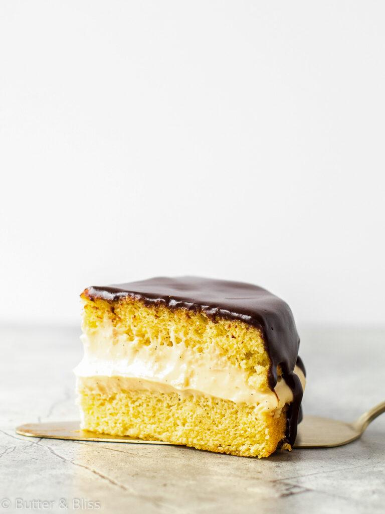 Slice of boston cream pie on a cake server