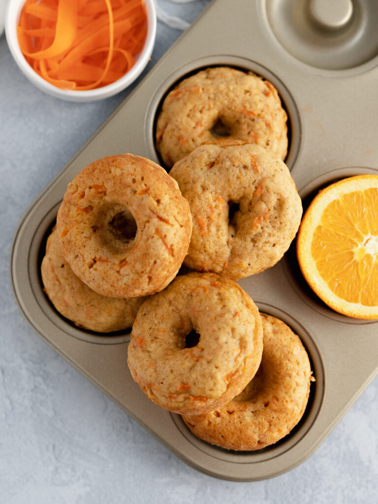 Fresh baked orange carrot donuts in a donut pan