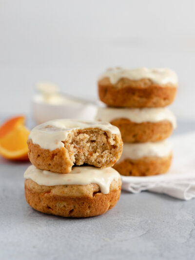 Stack of orange carrot donuts with a bite