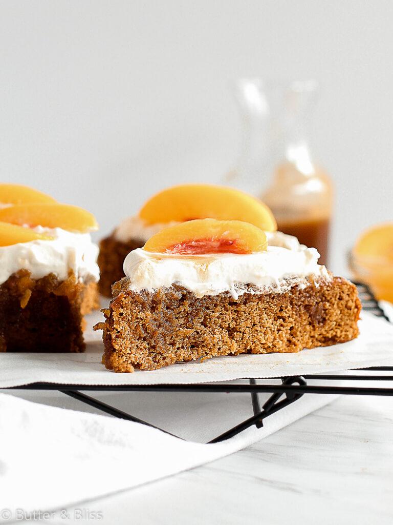 Slice of peach caramel cake on a wire rack