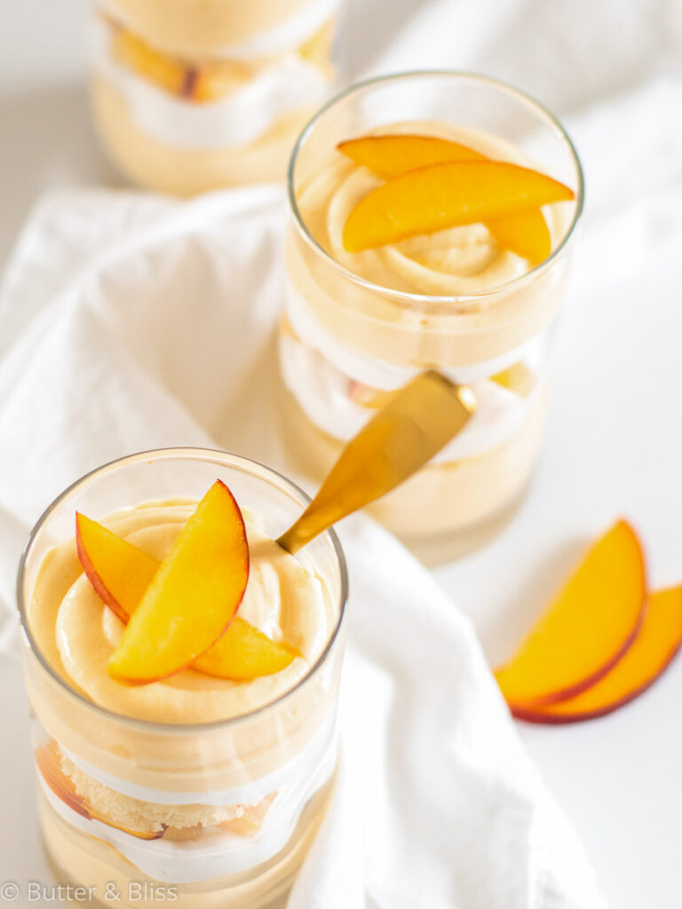 Peach mousse trifles in parfait glasses with spoons