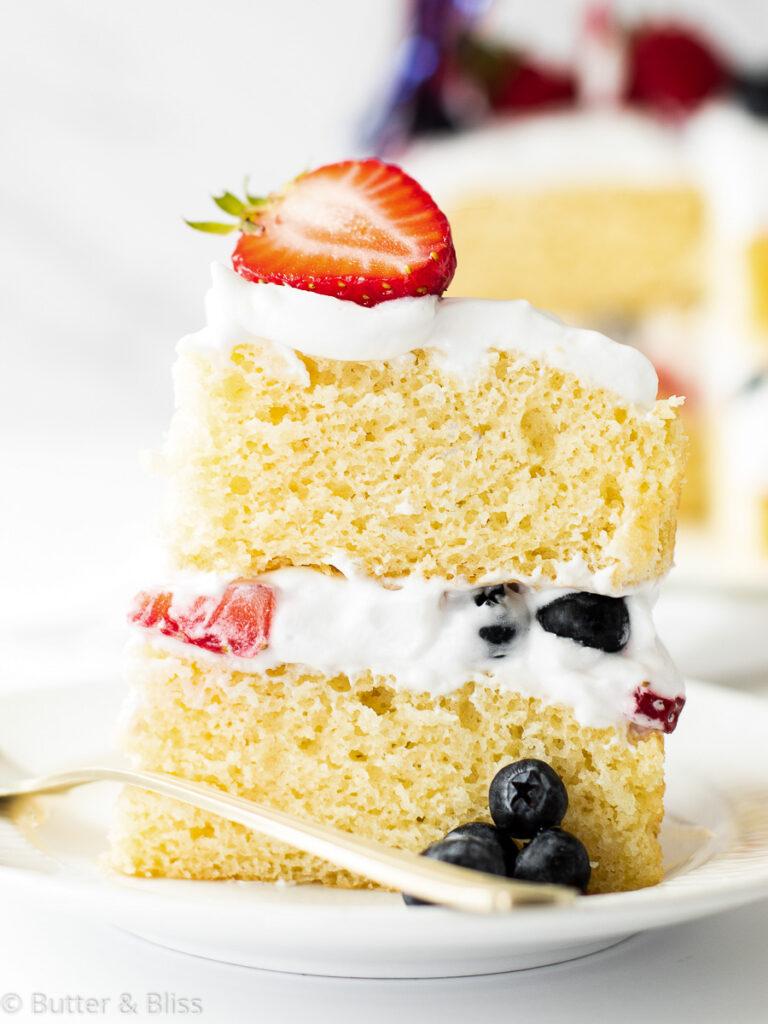 Slice of vanilla layered cake with berries