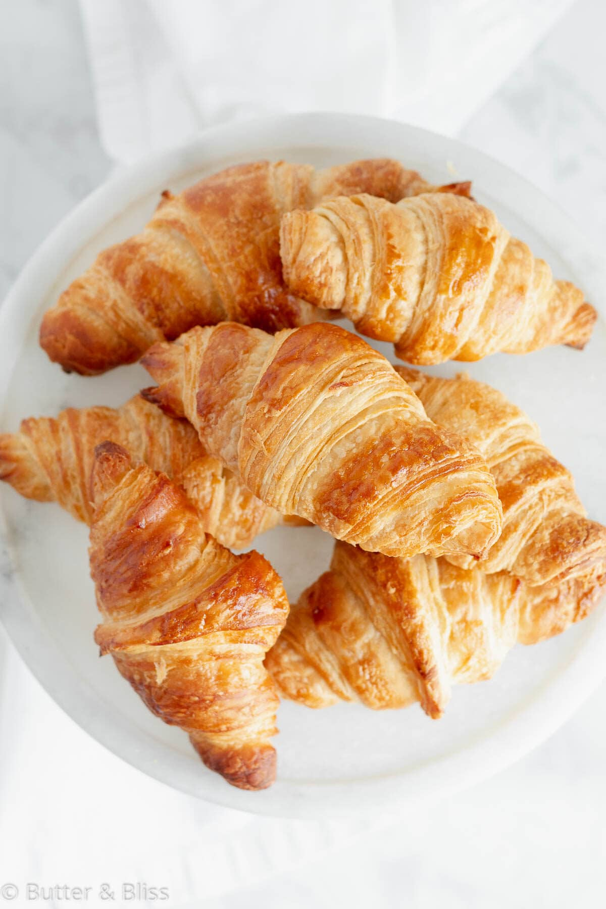 Top of homemade flaky croissants on a plate