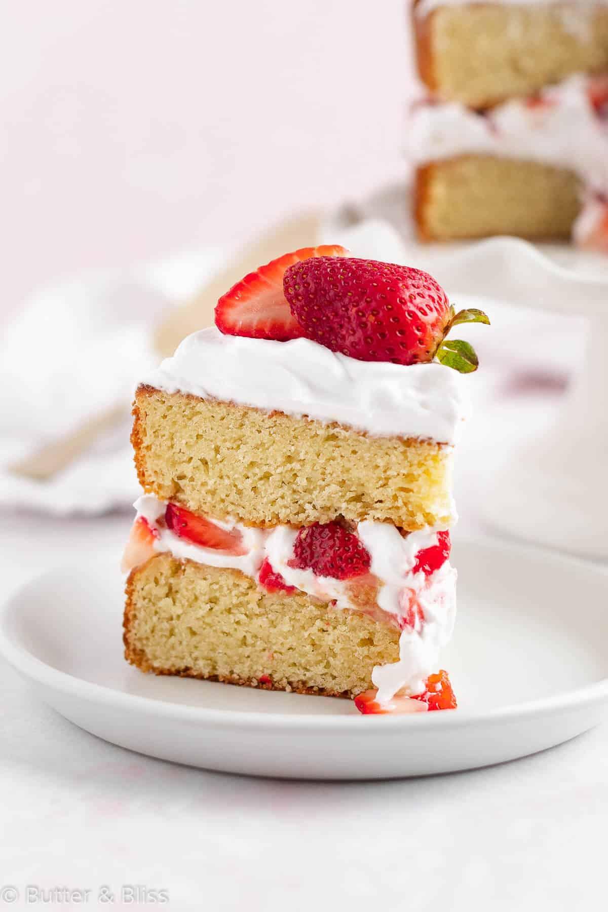Slice of fresh strawberry shortcake cake on a plate