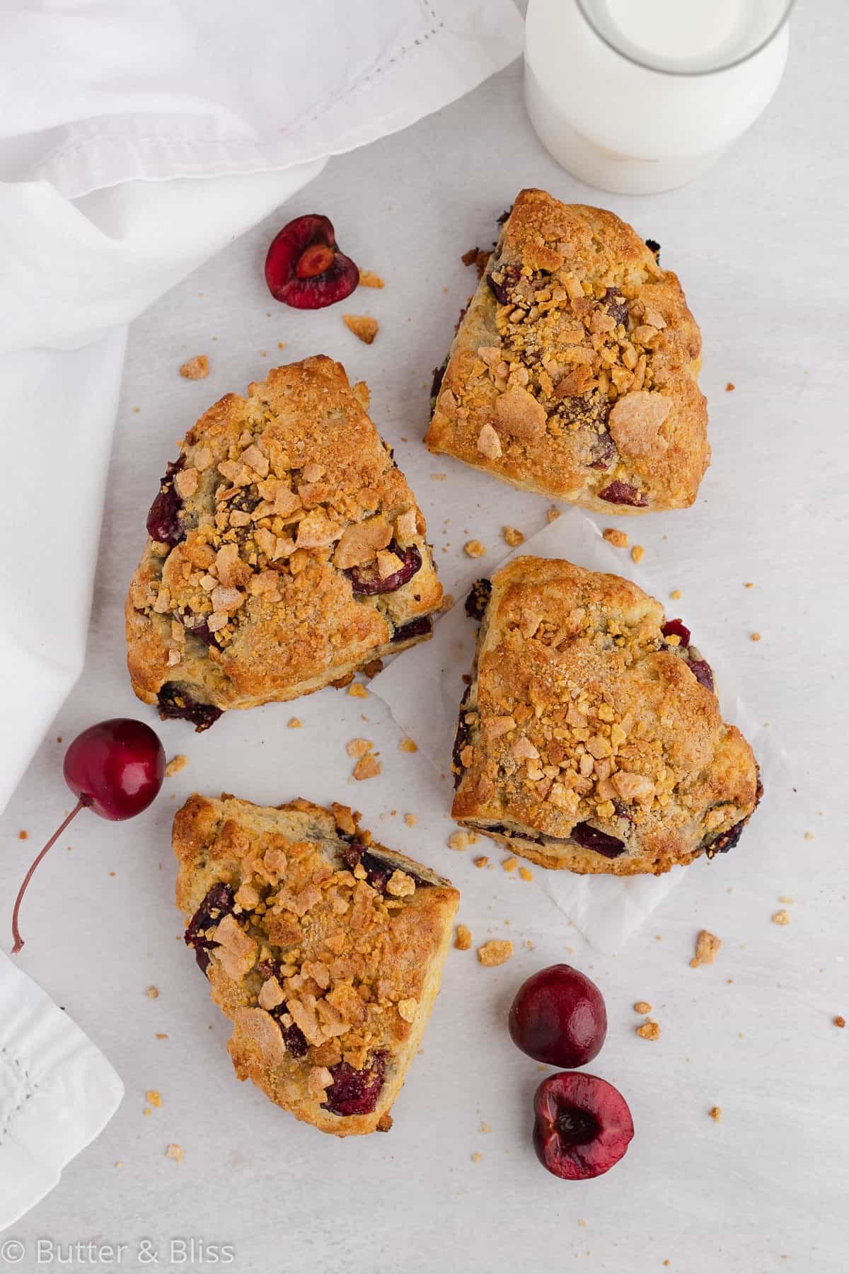 Four cherry scones on a table with fresh cherries