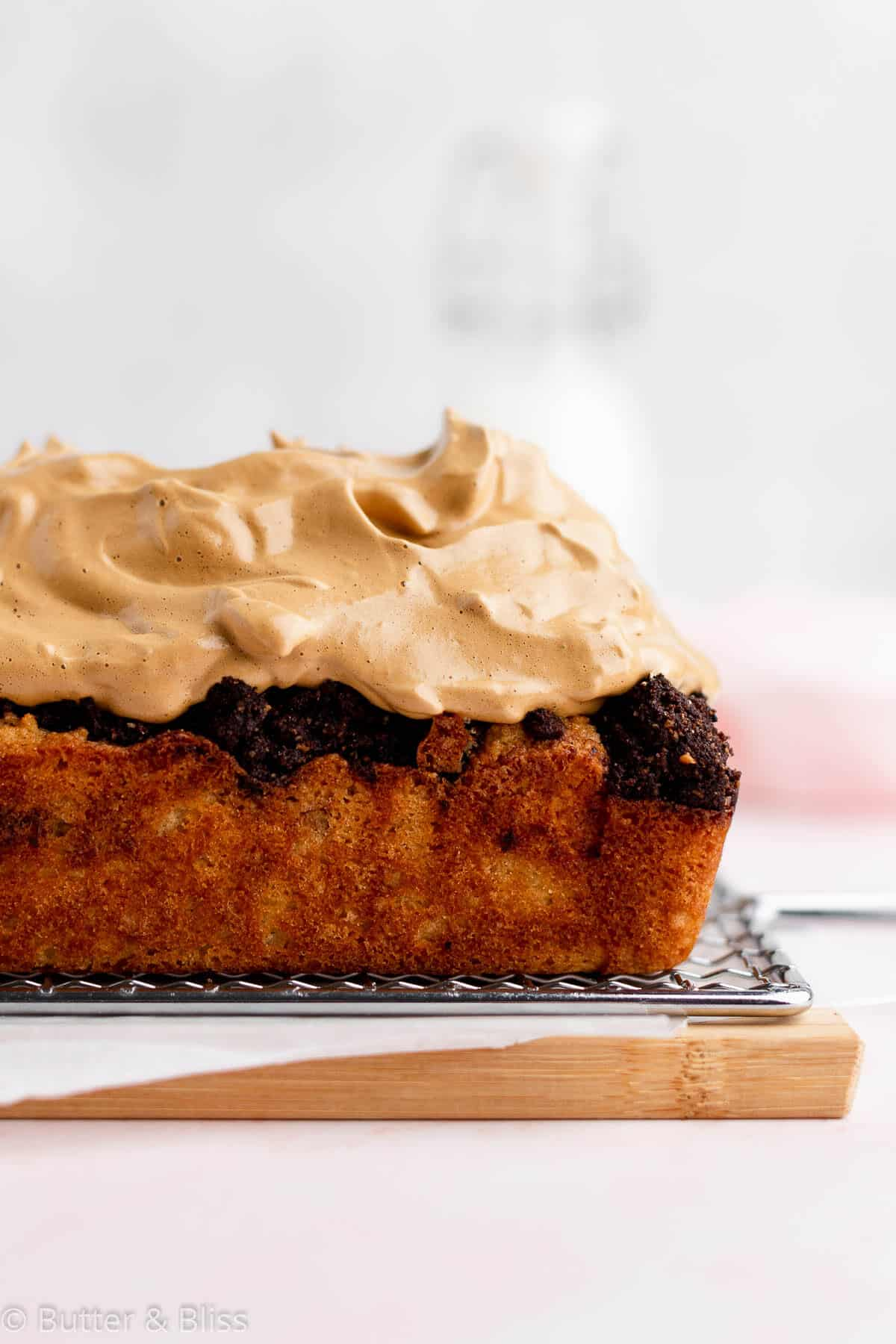Side view of a gluten free mocha coffee cake with dalgona whip