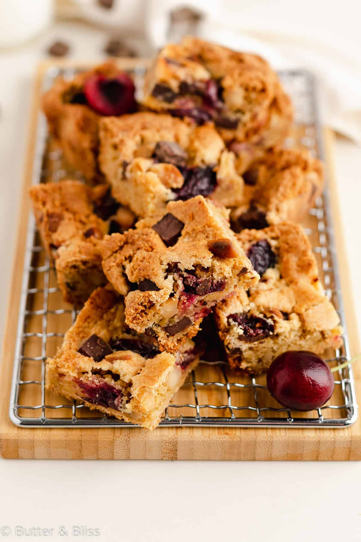 Gluten free cherry blondies cut into squares on a wire rack