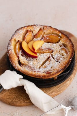 Peach clafoutis in mini cast iron skillet with powdered sugar