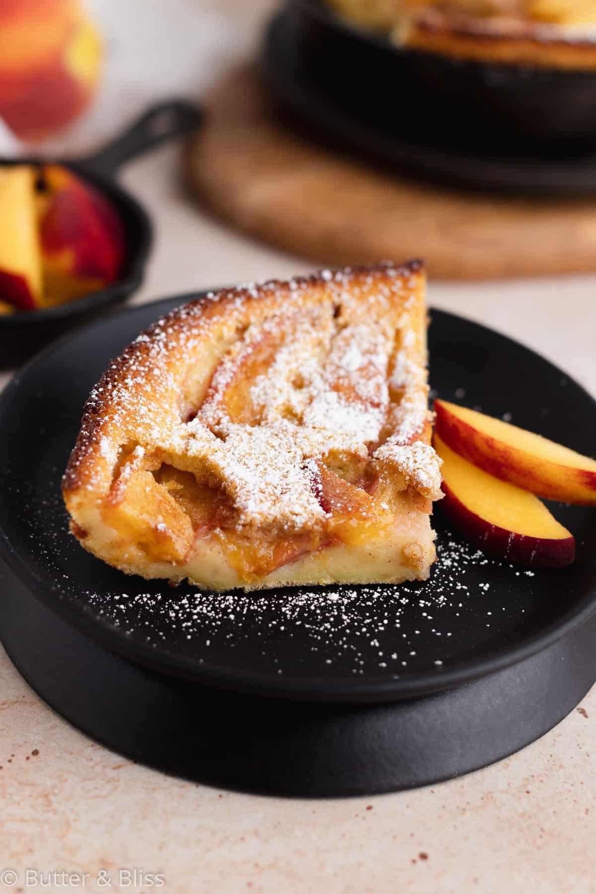 Slice of custardy peach clafoutis on a plate