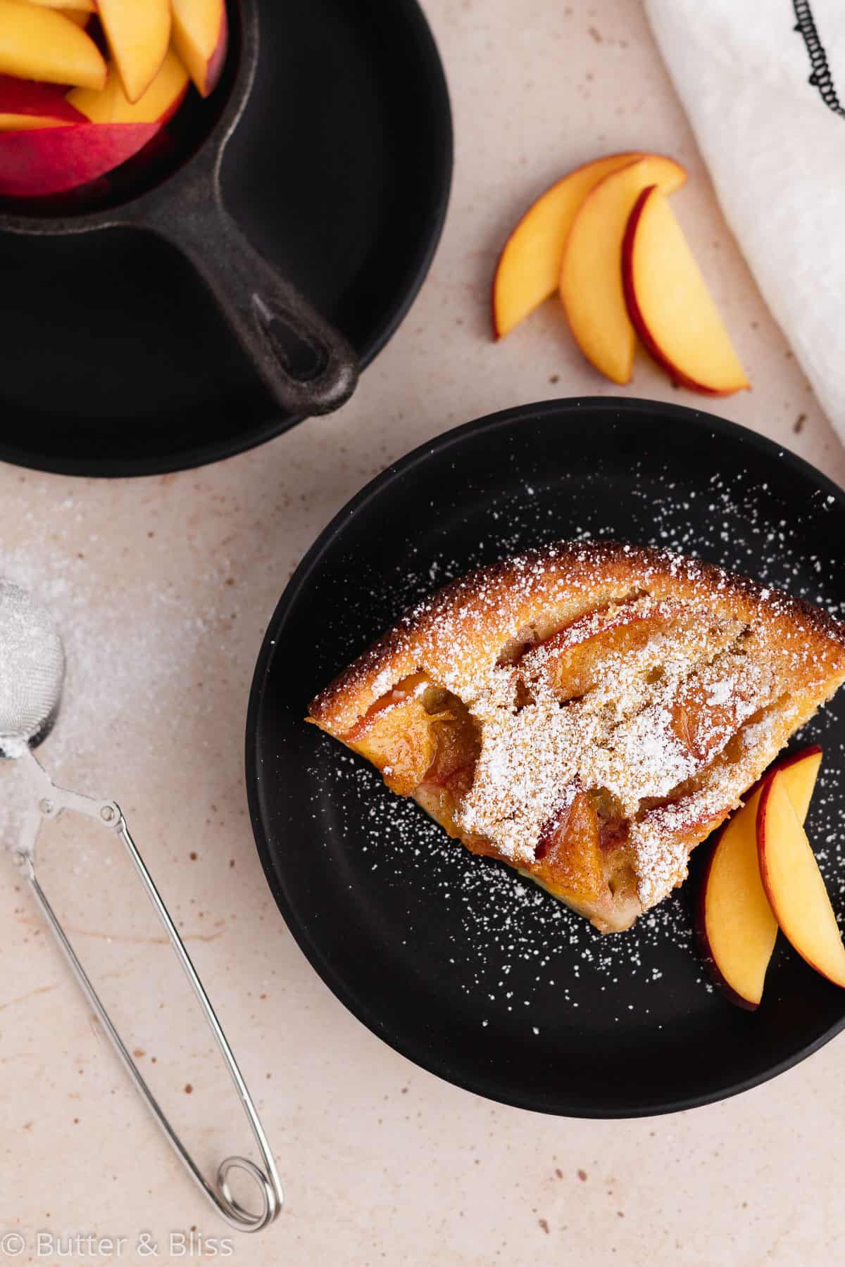 Top of a slice of peach clafoutis dusted with powdered sugar