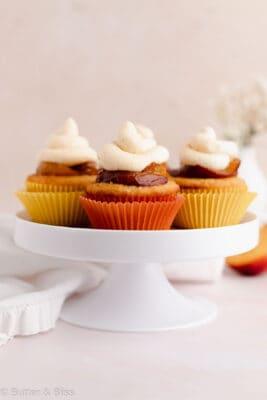 Gluten free peach cupcakes on a cupcake platter