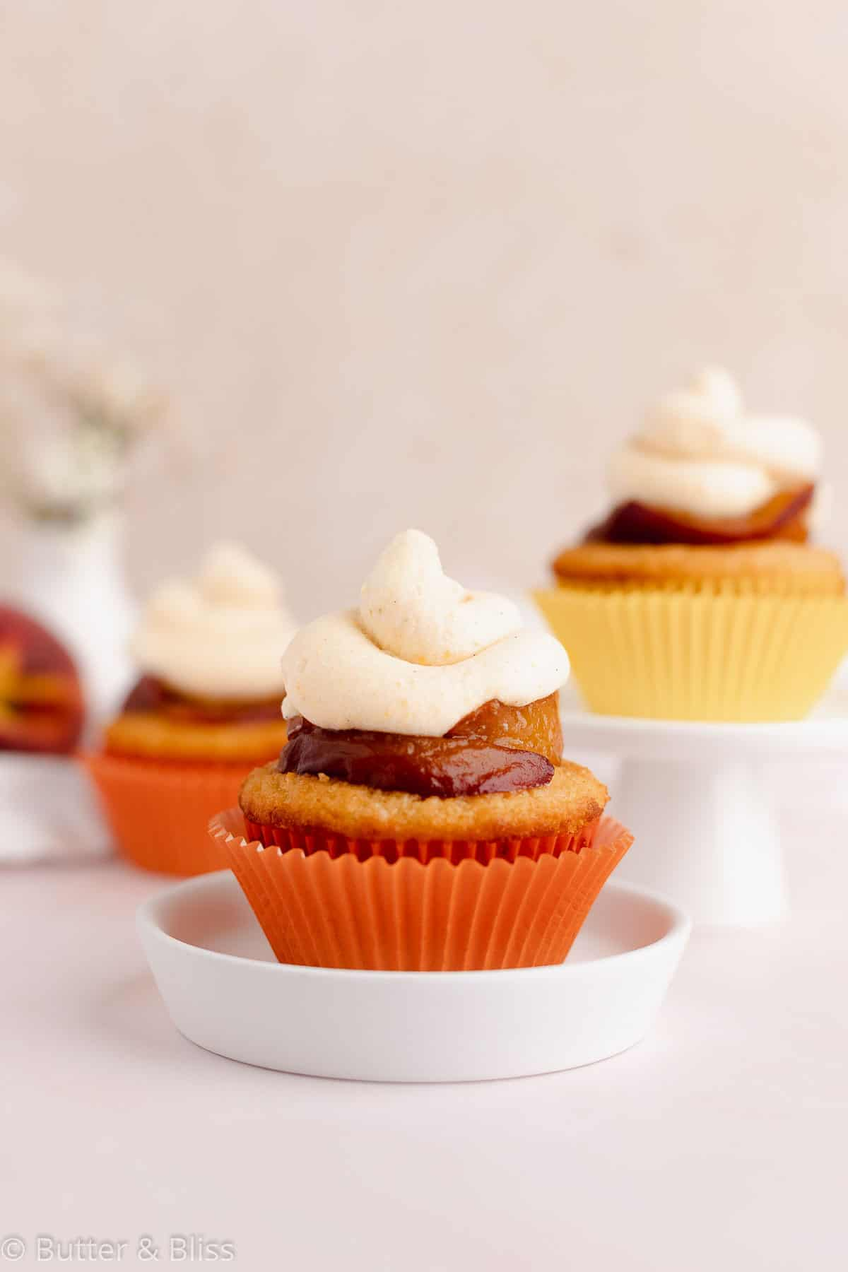 Close up of a single peach cupcake on a small plate
