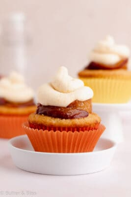 Single peach cupcake with peach frosting and caramelized peaches