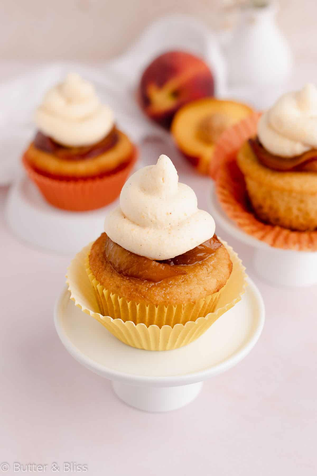 Small batch of peach cupcakes with peach frosting on a table