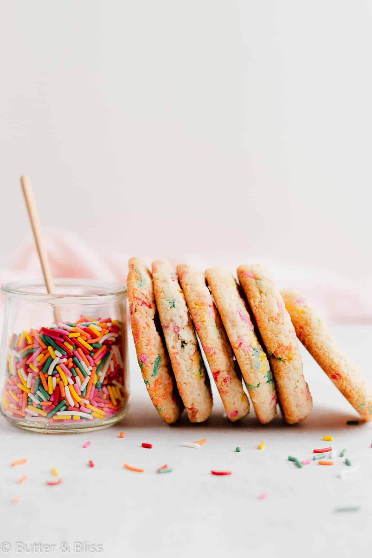 Gluten free funfetti sugar cookies stacked against a jar of sprinkles