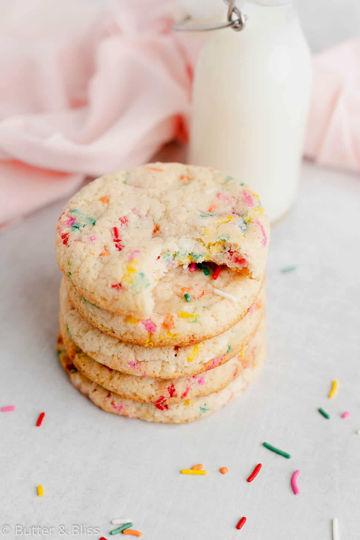 Stacked small batch sugar cookies with a jar of milk