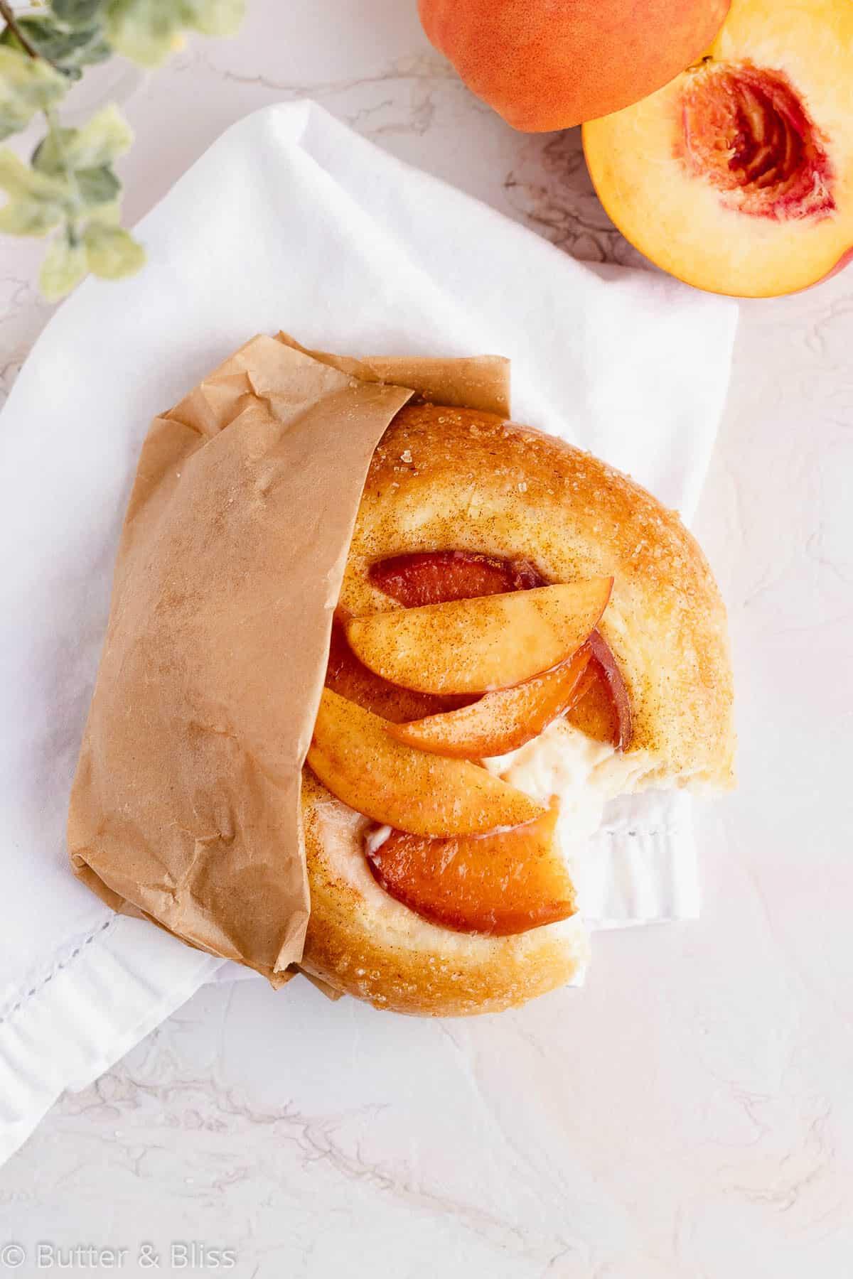 Top of a small batch peach kuchen in a paper wrapper