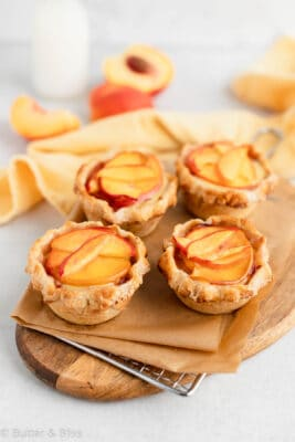 Fresh mini peaches and cream pies on a wooden platter
