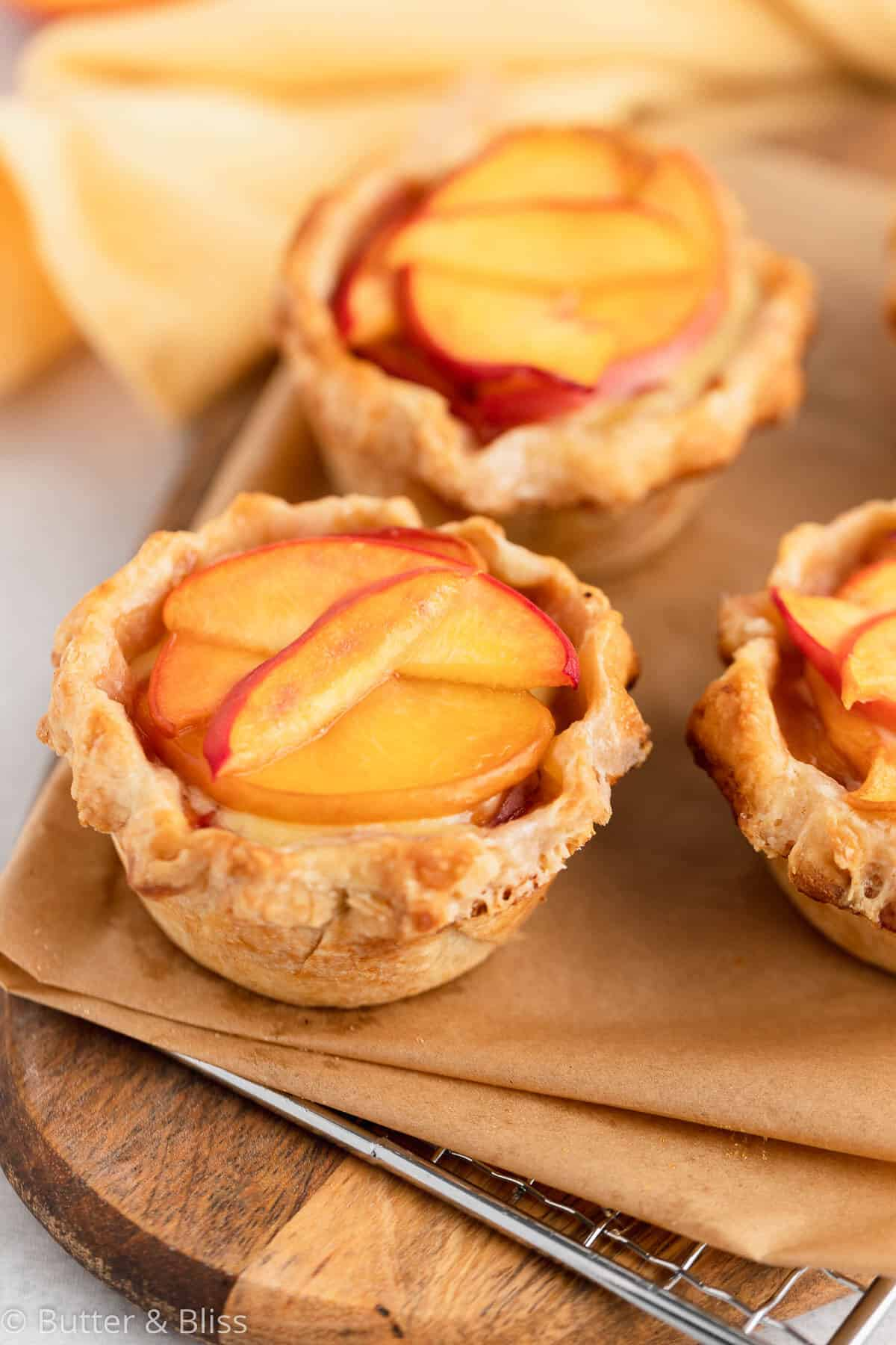 Fresh baked mini peaches and cream pies on a trivet