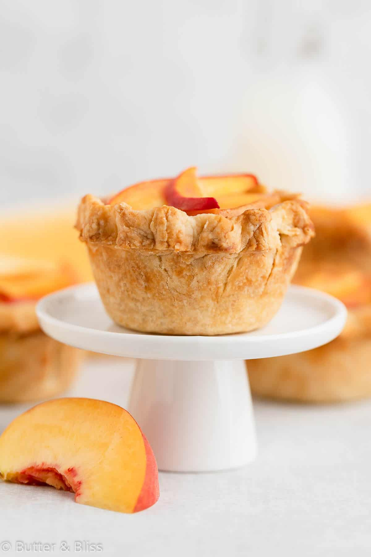 Flaky crust of a mini peach pie on a cupcake stand