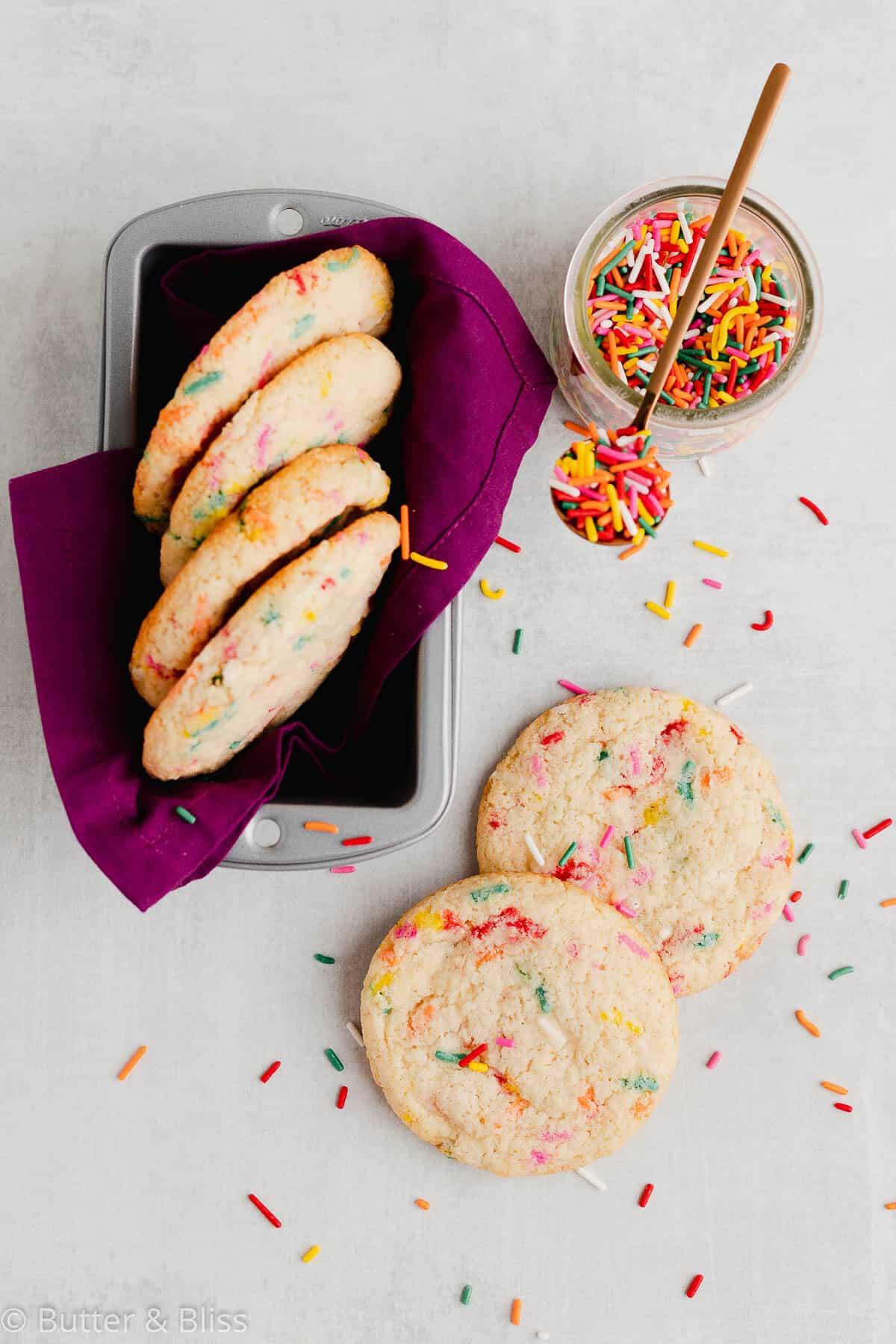 Sugar cookies with in a pan with a jar of sprinkles