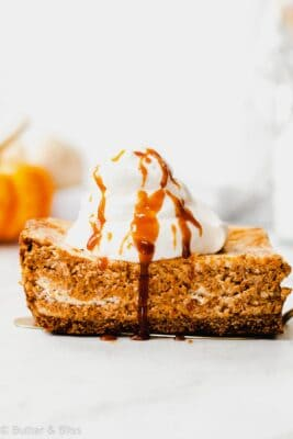 Slice of pumpkin swirl cheesecake topped with whipped cream