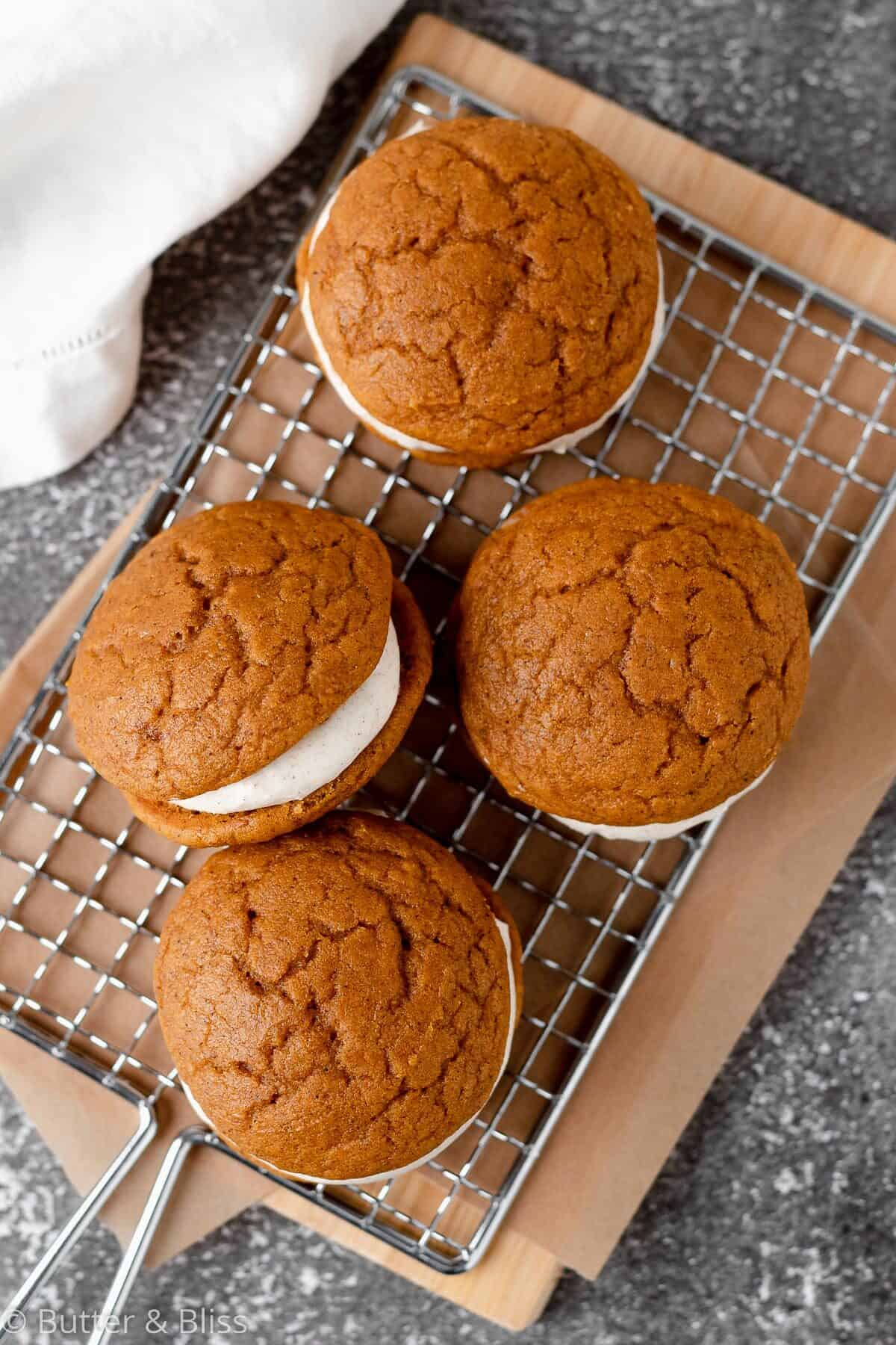 Pumpkin whoopie pies with cream cheese filling arranged on a wire rack