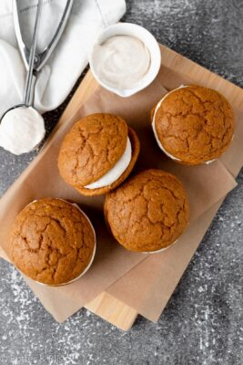 Pumpkin spice whoopie pies on a cutting board