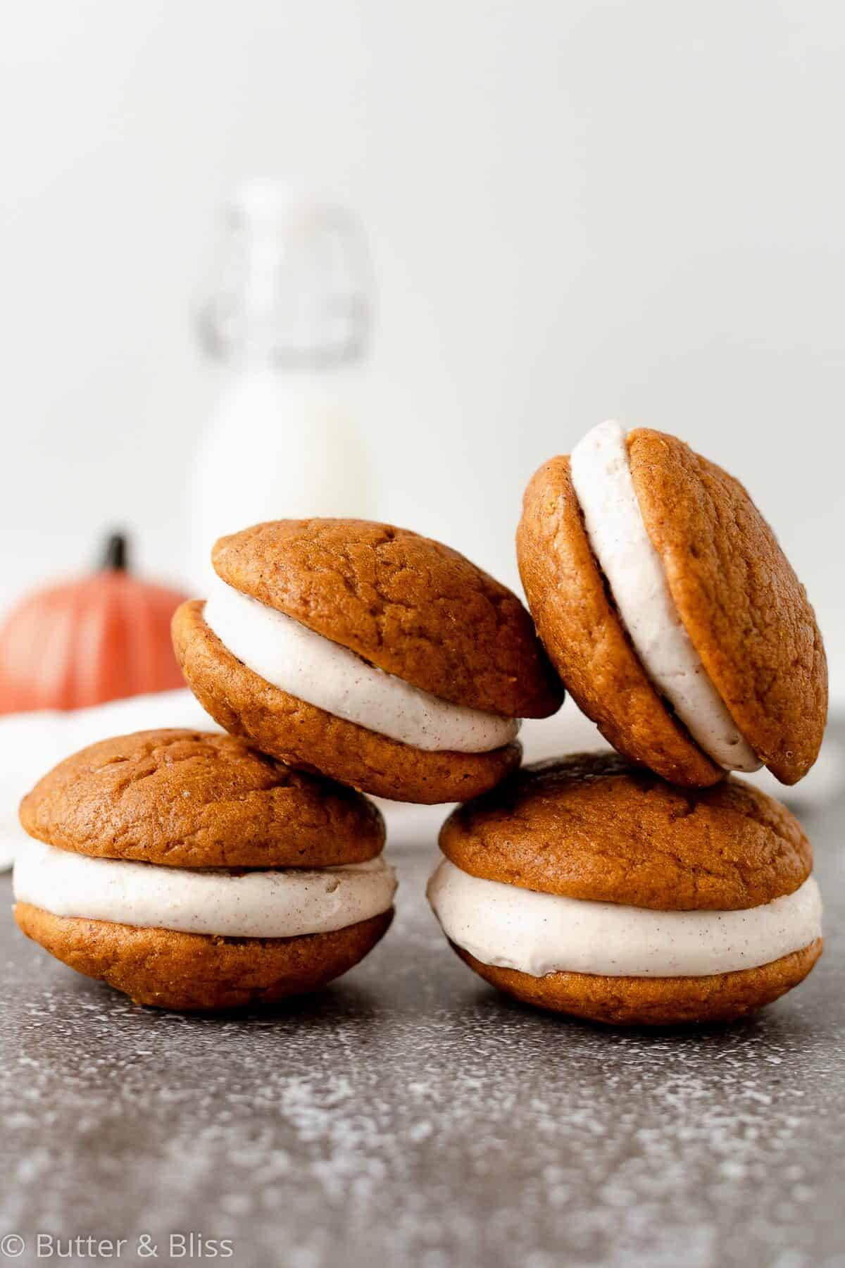 Pumpkin whoopie pies with cream cheese filling stacked in a pyramid