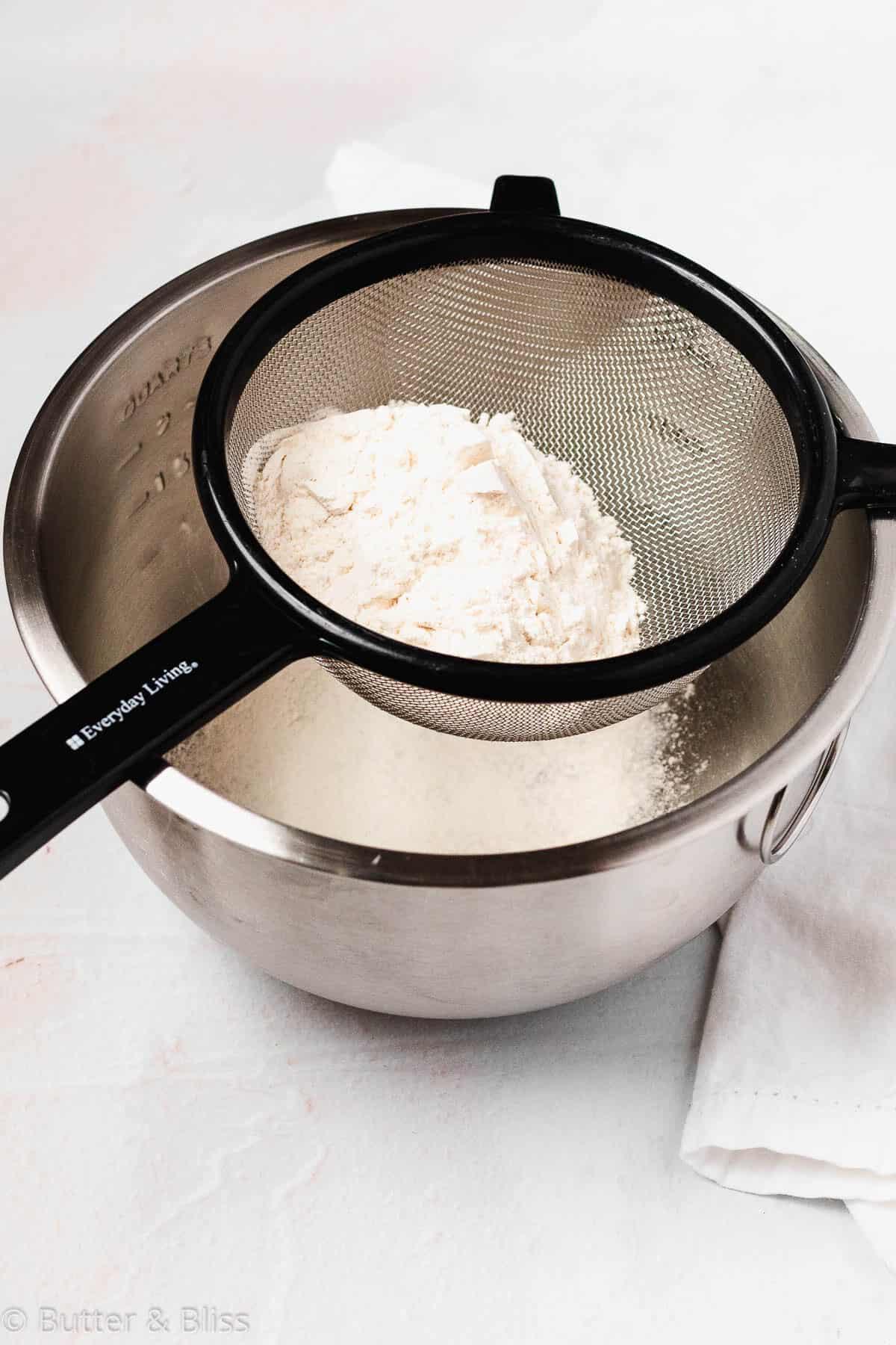 Sifting flour through a fine mesh strainer set over a bowl