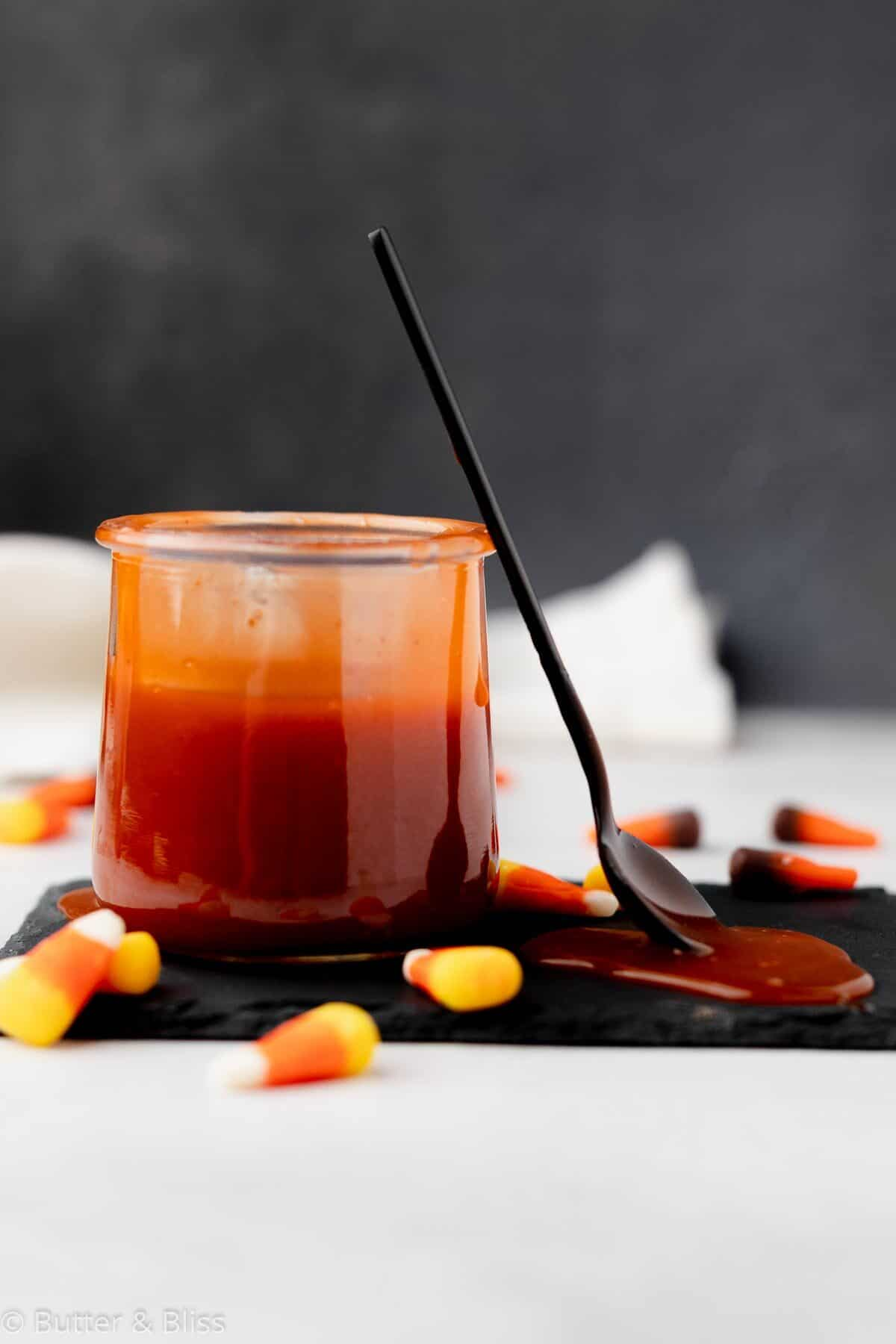 A jar of candy corn caramel sauce with a spoon