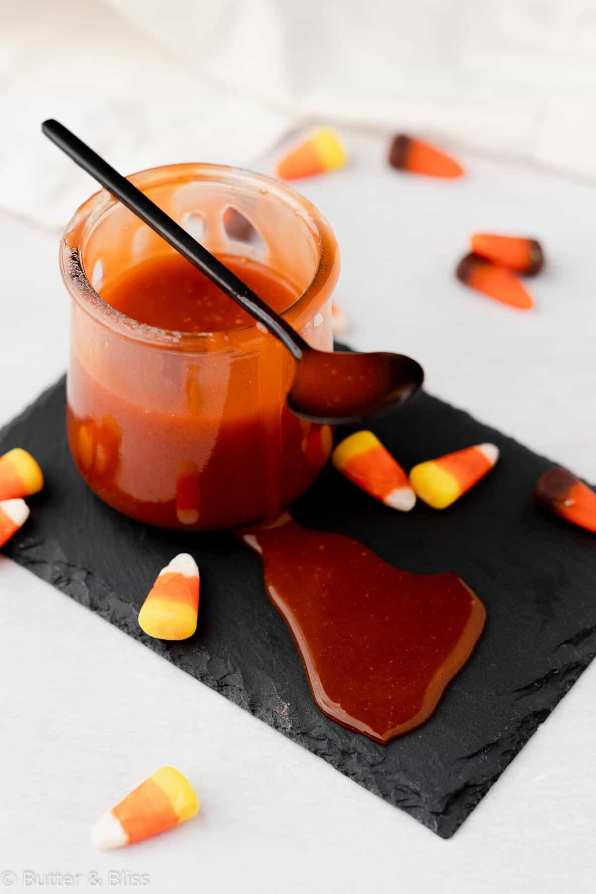 Candy corn caramel sauce in a small jar with a spoon