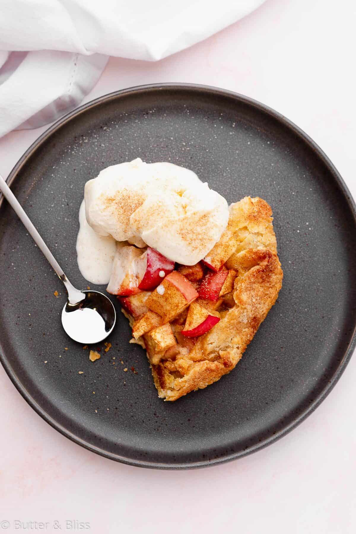 Slice of caramel corn apple galette on a plate with ice cream