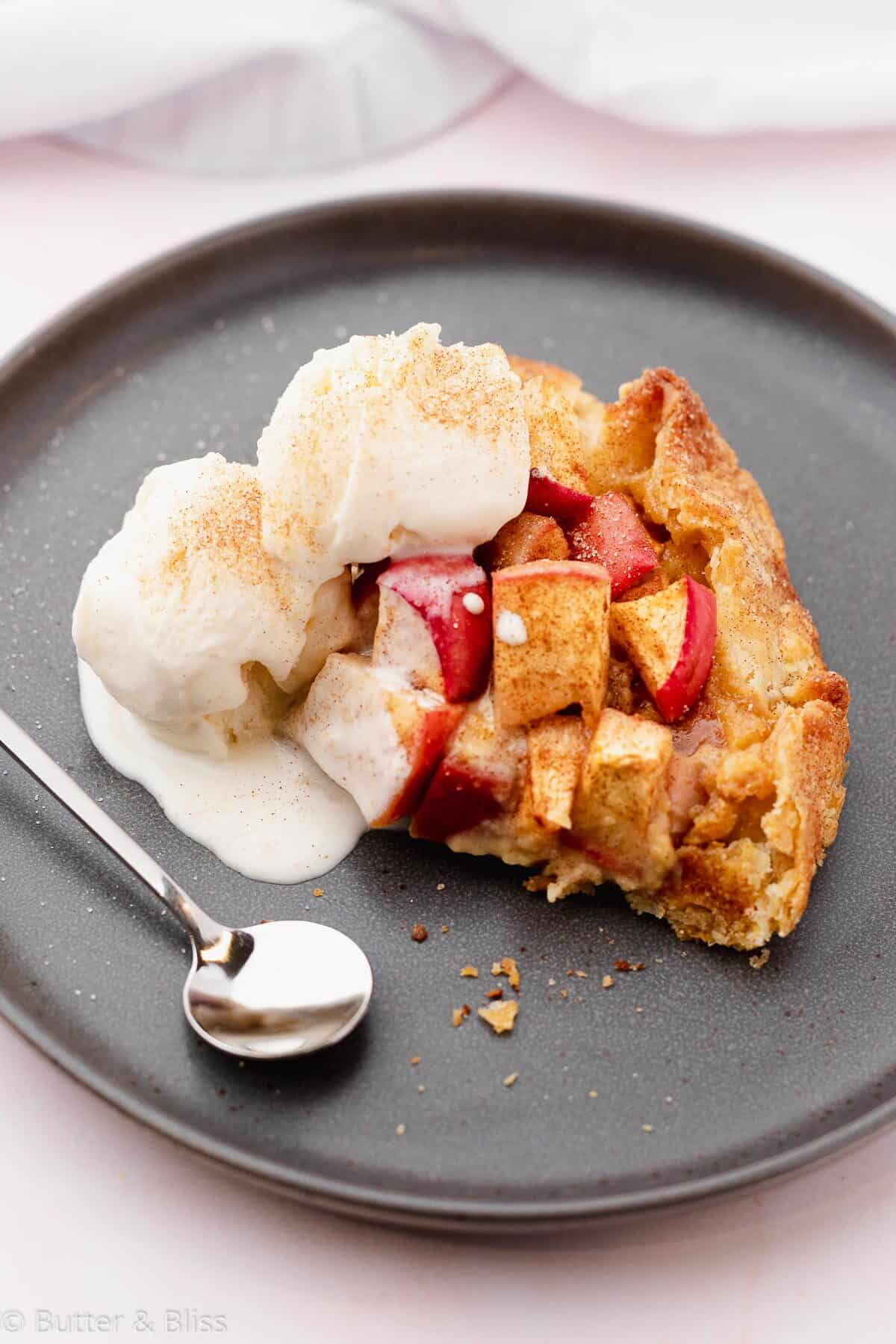 Slice of apple galette with ice cream on a plate